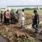 Warga yang melayat melihat kubangan air yang merenggut nyawa ketiga bocah di proyek jalan tol Solo-Kertosono, di Desa Ngasem, Colomadu, Karanganyar, Minggu (29/5/2016). (Iskandar/JIBI/Solopos)