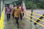 Gubernur DIY Sri Sultan Hamengku Buwono X (kedua dari kanan) melewati jembatan penyeberangan di atas Sungai Opak seusai meresmikan destinasi wisata Lava Bantal, Senin (30/5/2016). Meski tidak turun hujan, saat peresmian tengah terjadi banjir bandang di sungai Opak. (Sunartono/JIBI/Harian Jogja)