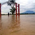 Seorang warga melintasi gapura pintu masuk Dukuh Bakung, Desa Pringanom, Masaran, Sragen yang tergenang air sedalam di atas lutut orang dewasa saat banjir melanda dukuh tersebut, Minggu (19/6/2016). (Tri Rahayu/JIBI/Solopos)