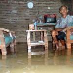 Mbah Narto duduk di kursi ruang tamu rumahnya yang tergenang air dengan ketinggian ai atas mata kaki, Minggu (19/6/2016). Rumah Mbah Narto terletak di RT 009, Dukuh Bakung, Desa Pringanom, Masaran, Sragen. (Tri Rahayu/JIBI/Solopos)