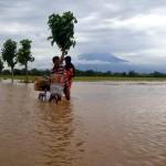 Warga membawa dagangan mi instan dengan menggunakan sepeda angin yang ditutun melewati genangan air di jalan masuk ke Dukuh Bakung, Desa Pringanom, Masaran, Sragen, Minggu (19/6/2016). (Tri Rahayu/JIBI/Solopos)