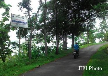 Seorang warga melintas di jalur menuju menara gantole di Sendang, Wonogiri, Selasa (28/6/2016). Jalur tersebut telah terpasang peringatan rawan longsor. (Bayu Jatmiko Adi/JIBI/Solopos)