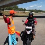 Setu, petugas jaga perlintasan sebidang di Karangturi, Gondangrejo, Karanganyar, memperingatkan pengendara sepeda motor yang melintas di jalan tol Soker, Rabu (29/6/2016) siang. (Kurniawan/JIBI/Solopos)