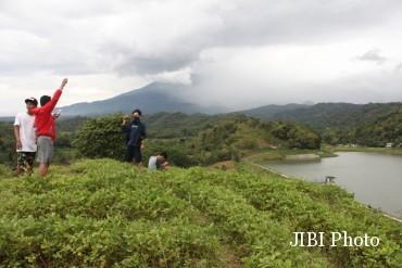 Sejumlah pemuda mengambil foto dengan latar belakang pemandangan Waduk Gebyar dan Gunung Lawu. Foto diambil belum lama ini. (Mariyana Ricky P.D./JIBI/Solopos)