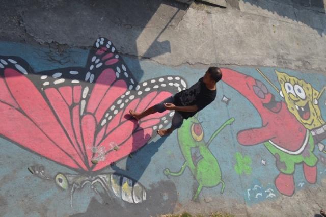 Seorang pejalan kaki melewati mural tiga dimensi berupa kupu-kupu raksasa dan animasi kartun spongebob di jalan perkampungan di Dusun Turiharjo, Desa Madegondo, Kecamatan Grogol, Jumat (26/8/2016). (Bony Wicaksono/JIBI/Solopos)