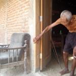 Sodimedjo alias Mbah Gotho, 146, berjalan membungkuk berpegangan pintu saat keluar dari dapur rumah di Dukuh Segeran RT 018/RW 008, Desa Cemeng, Kecamatan Sambungmacan, Sragen, Sabtu (27/8/2016). (Tri Rahayu/JIBI/Solopos)