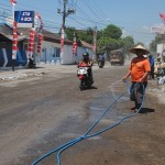 Warga menyirami jalan untuk mengurangi dampak debu akibat proyek perbaikan jalan Randusari-Kopen, Kecamatan Teras, Rabu (24/8/2016). (Hijriyah Al Wakhidah/JIBI/Solopos)