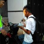 Anggota Polres Trenggalek, Brigadir Dedi Mahendra Sukma, saat menghukum salah satu pelajar yang tidak mengenakan helm saat mengendarai sepeda motor. (JIBI/Madiunpos.com/polrestrenggalek.com)