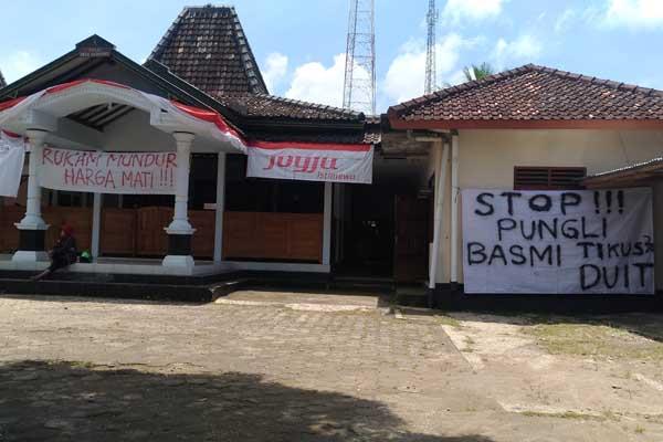 Warga Desa Dadapayu, Semanu memprotes dugaan pungutan liar yang dilakukan kepala desa setempat. Protes yang dituliskan di spanduk dipasang di balai desa setempat, Senin (17/10/2016). (Bhekti Suryani/JIBI/Harian Jogja)