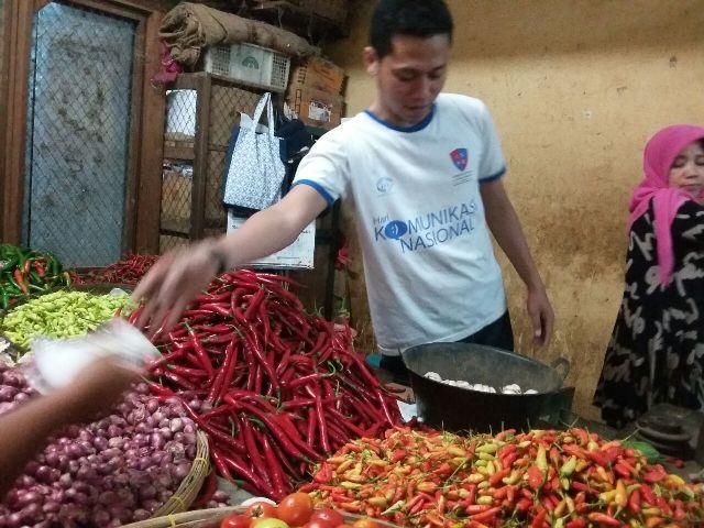 Seorang pedagang cabai dan sayuran di Pasar Songgolangit Ponorogo melayani pembeli, Jumat (30/12/2016). (Abdul Jalil/JIBI/Madiunpos.com)