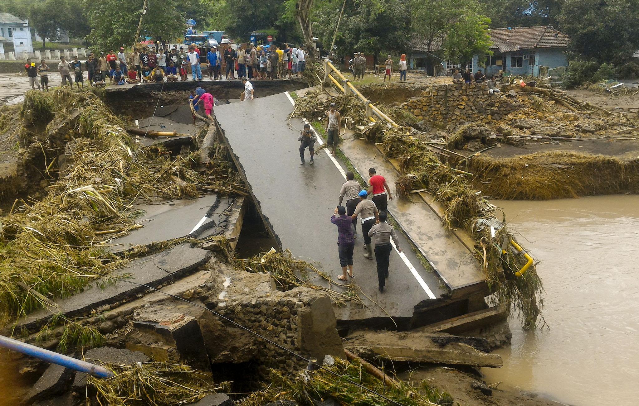 Warga berada dekat jembatan yang ambruk diterjang banjir di Kelurahan Kodo, Kecamatan Rasana'e Timur, Kota Bima, NTB, Kamis (22/12/2016). Banjir yang terjadi akibat meluapnya air sungai Padolo ini melumpuhkan seluruh aktifitas warga di Bima. (JIBI/Solopos/Antara/Didin)