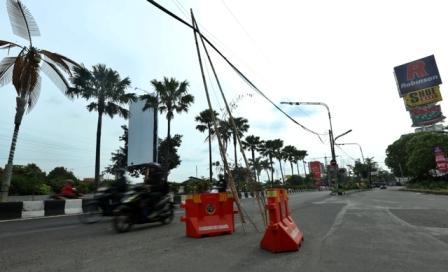Kabel telekomunikasi melintang rendah dan hanya disangga bambu di Jl. Slamet Riyadi, Purwosari, Solo, Senin (26/12/2016). (Nicolous Irawan/JIBI/Solopos)
