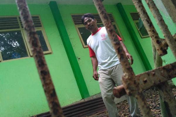 Penjaga SMP Negeri 3 Pleret saat hendak memeriksa pintu pagar besi yang dibuka paksa oleh pencuri, Senin (26/12/2016). (Arief Junianto/JIBI/Harian Jogja)