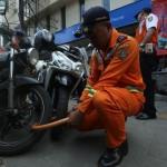 Petugas Dinas Perhubungan (Dishub) Kota Solo menggembok roda sepeda motor yang diparkir di trotoar, Jl. Gatot Subroto, Singosaren, Solo, Jumat (10/2/2017). (Nicolaus Irawan/JIBI/Solopos)