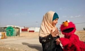 Boneka Elmo memberikan pelajaran kepada seorang anak korban perang Suriah (Voanews.com)