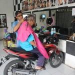 Andri Susanto, 20, salah satu tukang cukur di Raja Cukur Klaten, memangkas rambut pemilik usaha Yatin, 74, yang duduk di sepeda motor, Rabu (15/3/2017). (Taufiq Sidik Prakoso/JIBI/Solopos)
