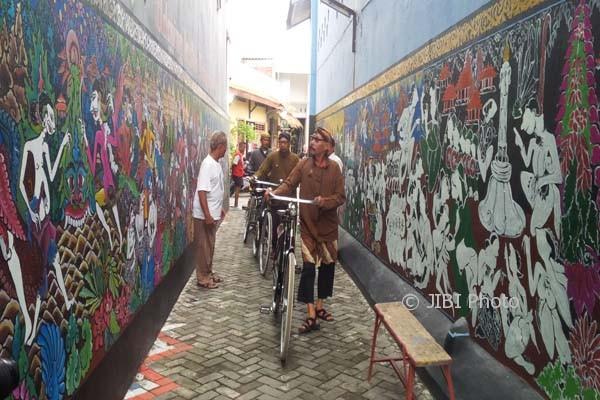 Komunitas pencinta sepeda onthel Kota Semarang saat melewati gang di Kampung Batik Tengah yang dinding bangunannya dihiasi lukisan tentang sejarah berdirinya Kota Semarang, Kamis (9/4/2017). (JIBI/Semarangpos.com/Imam Yuda S.)
