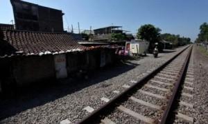 Warga melintas di depan rumah yang terdampak proyek jalur kereta api (KA) Bandara Adi Soemarmo di Kadipiro, Solo, Selasa (23/5/2017). (M. Ferri Setiawan/JIBI/Solopos)