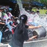 Seorang wanita menyiramkan air ke rombongan konvoi kelulusan pelajar di Lapangan Gulun, Kota Madiun, Rabu (3/5/2017). (Istimewa/Facebook: Andy Matahati)