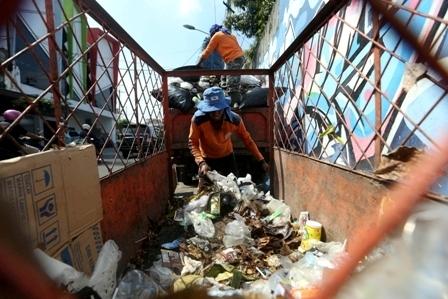 Ilustrasi petugas kebersihan memindahkan sampah dari gerobak ke mobil pengangkut sampah. (Nicolous Irawan/JIBI/Solopos)