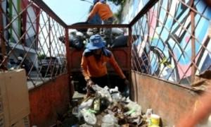 Petugas kebersihan memindahkan sampah dari gerobak ke mobil pengangkut sampah di Jl. Saharjo, Kampung Baru, Pasar Kliwon, Solo, Senin (12/6/2017). (Nicolous Irawan/JIBI/Solopos)
