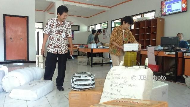 Kepala Kantor Pos Sukoharjo, Tatik Nurhayati (kanan) mengecek barang paket yang dikirim melalui kantor pos, Jumat (9/6/2017). (Trianto Hery Suryono/JIBI/Solopos)