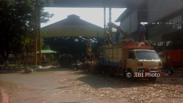 Pekerja memindahkan tebu dari lori ke truk di PG Pagottan di Madiun untuk kemudian dikirimkan ke pabrik gula lain milik PTPN XI, Minggu (23/7/2017). PG Pagottan berhenti beroperasi akibat evaporator meledak dan mengakibatkan tiga pekerja terluka, Jumat (21/7/2017). (Miftahul Ulum/JIBI/Bisnis)