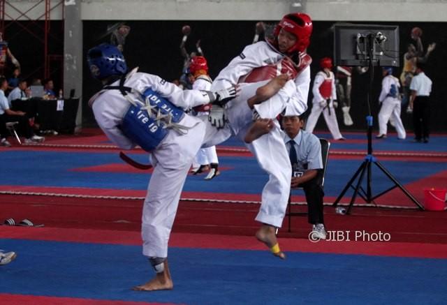 Taekwondoin asal Semarang, Arya Bagus (kanan), berhasil memblok tendangan taekwondoin asal Solo, Mochamad Fachru Noer (kiri), pada kelas Junior Male Under 55kg dalam Kejuaraan Daerah Jawa Tengah 2017 Junior-Senior di Sritex Arena, Solo, Minggu (6/8). (JIBI/Solopos/M. Ferri Setiawan)