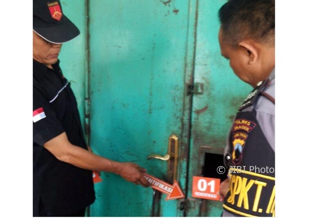Dua polisi memeriksa kunci kios milik Sugiyono di Pasar Plupuh, Sragen, yang dibobol maling, Kamis (10/8/2017). (Istimewa/AKP Winarso)