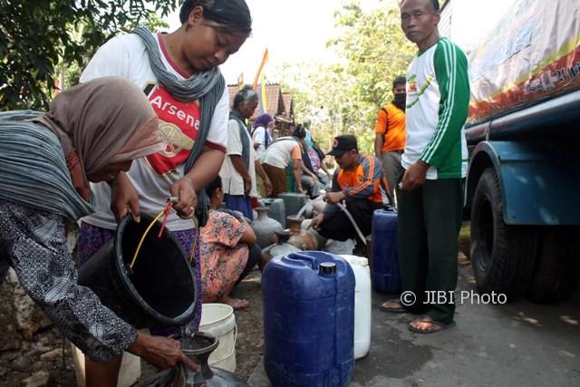 Warga menuang air ke dalam kelenting milik warga lainnya saat antre bantuan air bersih dari BPBD Sragen di Dukuh Kowang, Desa Ngargotirto, Sumberlawang, Sragen, Sabtu (12/8/2017). (Tri Rahayu/JIBI/Solopos)