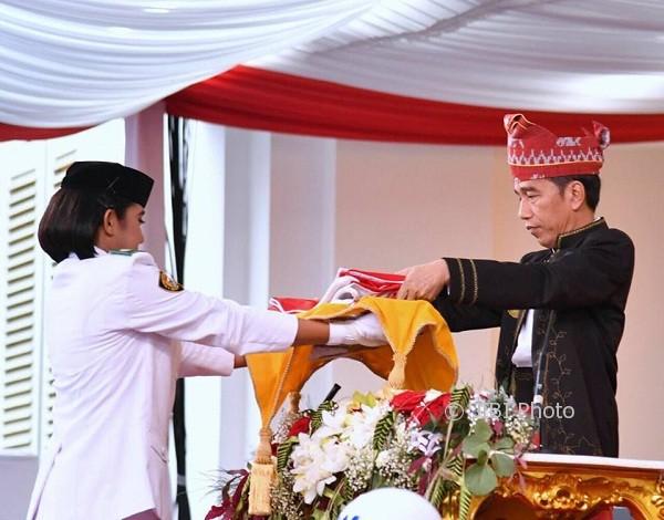 Presiden Joko Widodo mengambil bendera dari pembawa baki, Ruth Celine Eglesya Purba, saat Upacara Penurunan Bendera, Kamis (17/8/2017) di Istana Merdeka. (Facebook)