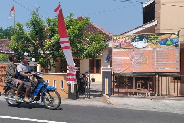 Warga melintas di depan baliho berisi informasi APBDes Kradenan, di Desa Kradenan, Trucuk, Senin (7/8/2017). (Cahyadi Kurniawan/JIBI/Solopos)