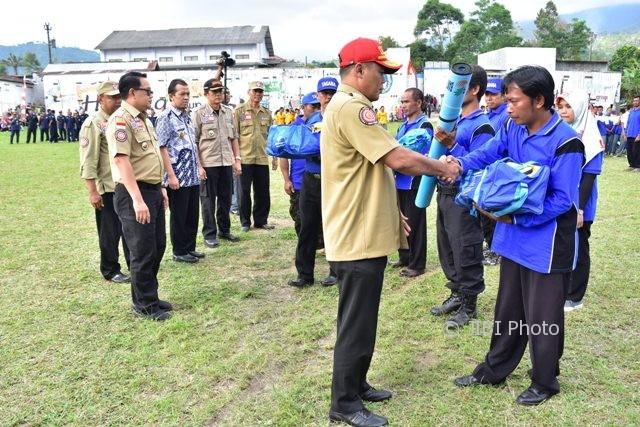 Bupati Karanganyar, Juliyatmono (topi merah), menyerahkan bantuan peralatan kepada warga Desa Girimulyo, Ngargoyoso, yang menjadi pengurus kampung siaga bencana saat pengukuhan kampung siaga bencana pada Jumat (4/8/2017). (Istimewa/Dokumentasi Dinas Kominfo Karanganyar)