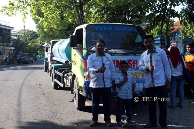 Dua pengurus Himpi Sragen berpose di depan mobil tangki yang membawa air bersih untuk ratusan keluarga di Galeh, Tangen, Sragen, Sabtu (16/9/2017). (Tri Rahayu/JIBI/Solopos)