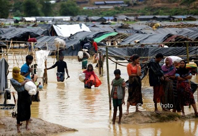 Pengungsi Rohingya meninggalkan tempat penampungan darurat di Cox's Bazar Bangladesh yang dilanda banjir saat hujan lebat, Selasa (19/9/2017). (JIBI/Solopos/Reuters/Mohammad Ponir Hossain)