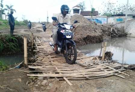 Seorang pengendara menyeberangi sungai di Kelurahan Lalung lewat jembatan anyaman bambu pada Jumat (13/10/2017). (Sri Sumi Handayani/JIBI/Solopos)