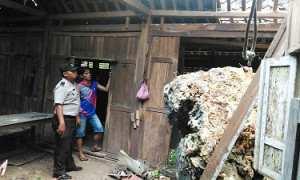 Salah seorang petugas dari Polsek Purwosari sedang memeriksa batu besar yang menjebol sebagian rumah milik Adi Tiryono di Dusun Nglegok, Giritirto, Purwosari. Minggu (29/10/2017). (Istimewa/Polsek Purwosari)