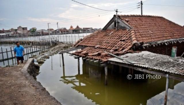 Warga melintasi rumah yang ditinggal pemiliknya akibat terendam rob di Kampung Tambakrejo, Tanjung Emas, Kota Semarang, Jateng, Rabu (4/10/2017). (JIBI/Solopos/Antara/Aditya Pradana Putra)