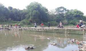 Warga melintasi jembatan dari anyaman bambu atau sasak yang menghubungkan Mojolaban, Sukoharjo, dengan Beton, Sewu, Jebres, Solo, Jumat (27/10/2017). (Nicolous Irawan/JIBI/Solopos)