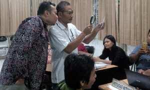 Ketua KPU Kota Jogja Wawan Budianto (kiri) turut menyaksikan pengecekan KTP dengan alat bantu kaca pembesar, Selasa (17/10/2017). (Ujang Hasanudin/JIBI/Harian Jogja)