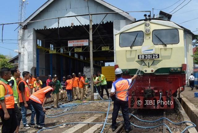 Taruna dan taruni Akademi Perkeretaapian (API) serta Komunitas Pencinta Kereta Api mencuci lokomotif BB30125 di Dipo Lokomotif PT Kereta Api Indonesia (KAI) Daerah Operasi VII Madiun, Minggu (1/10/2017).(JIBI/Solopos/Antara/Siswowidodo)