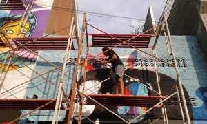Seorang seniman melukis mural di salah satu pertokoan koridor Jalan Gatot Subroto (Gatsu), Selasa (24/10/2017). (Ika Yuniati/JIBI/Solopos)