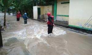 Sejumlah sukarelawan bencana alam mengevakuasi warga menggunakan tali saat banjir akibat luapan air Kali Siluwur merendam rumah warga Desa Karangwuni, Weru, Selasa (28/11/2017). (Istimewa)