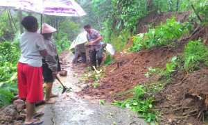 Kanit Binmas Polsek Ngargoyoso, Aiptu Edi H., bersama warga bekerja bakti membersihkan bekas tanah longsor di Ngargoyoso, Selasa (28/11/2017). (Istimewa/Dokumentasi Polres Karanganyar)