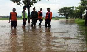 Tim TNI, Polri, dan BPBD Sragen dibantu warga berpatroli di jalan penghubung Desa Tangkil dan Desa Kedungupit, Sragen Kota, yang tergenang air, Rabu (29/11/2017). (Tri Rahayu/JIBI/Solopos)