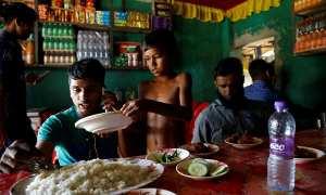 Seorang bocah pengungsi Rohingya, Azimul Hasan, menyajikan makanan di restoran tempat kerjanya di Jamtoli, Bangladesh, Minggu (12/11/2017). (JIBI/Reuters/Navesh Citrakar)