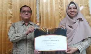 Rektor UII Nandang Sutrisna (kiri) dan Kepala Badan Penjaminan Mutu UII Kariyam (kanan) menunjukkan sertifikat SNI, Rabu (22/11/2017). (Harian Jogja/Sunartono)