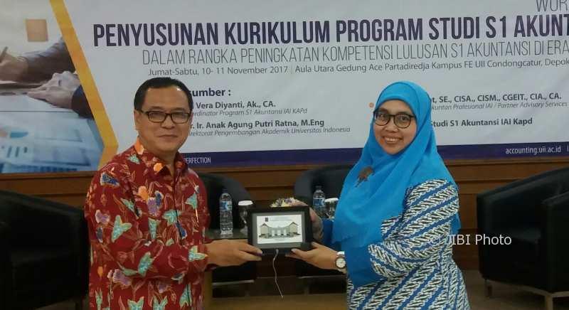 Rektor UII Nandang Sutrisna (kiri) menyerahkan cinderamata kepada salah satu narasumber workshop penyusunan kurikulum, Jumat (10/11/2017). (Harian Jogja/Sunartono)