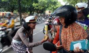Polwan memberi hadiah kepada anak laki-laki yang mengenakan helm saat Operasi Zebra Candi 2017 di Jl. Diponegoro Sragen, Sabtu (11/11/2017). (Tri Rahayu/JIBI/Solopos)