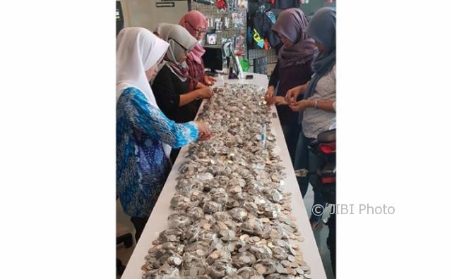 Karyawan menghitung uang logam yang digunakan Eko Margono dan Ernawati untuk membeli sepeda motor sport Kawasaki Ninja 250 Fidi dealer Kawasaki di Madiun. (Instagram @kawasaki_madiun)